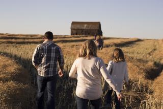 Family walking through golden field toward barn 8-18