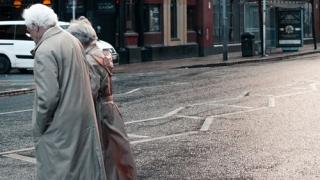 Older couple crossing city street 4-19