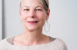Older woman with sweatshirt and dangling earrings 8-18