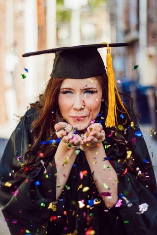 Girl in Graduation Cap and Gown blowing confetti 8-18