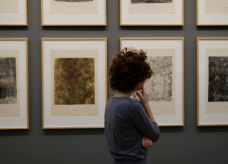 Woman looking at artwork pensively 8-18