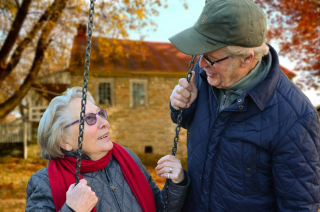 Older couple wife on swing with husband holding 8-18