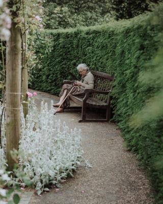 Older woman on bench in nursing home garden 4-19