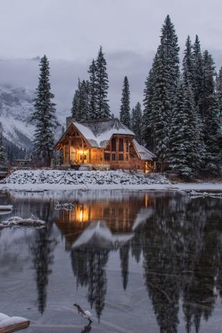 Large log home on lake with snow 3-19