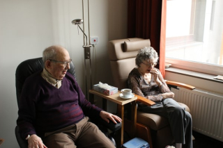 Couple sitting in assisted living apartment 10-19