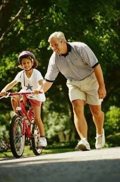 Dad teaching son to ride bike 3-19