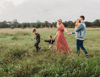Farm Woman holding man and toddlers hands in field  10-19
